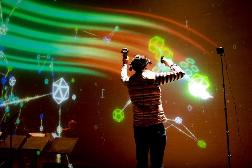 """DJ Spooky creates 3D visuals and triggers sounds in VR using custom app designed by MEDIUM Labs, backed by live acoustic musicians and singers, effectively creating a live """"internet symphony"""" on stage."""