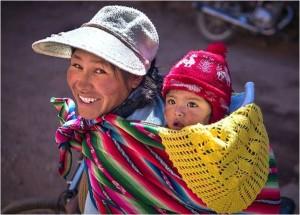 [Fotografía de Omnifoto-J. Alberto Mariñas que muestra a una madre con su bebé a cuestas en la localidad peruana de Pucará].