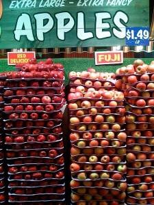 """Manzanas Red delicious y las Fuji (derecha), bajo un cartel que dice """"Manzanas extra grandes, extra lujosas"""" (Wikipedia)"""