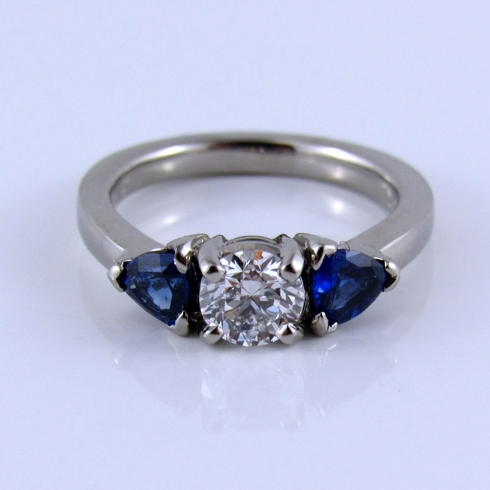 Diamond and Sapphire Engagement Ring - Classic and elegant, this sweet engagement is a timeless classic. The diamond is a 0.50 carat Canadian diamond that is set off by two beautiful brilliant trillion shaped sapphires.#CanadianDiamond #ThreeStoneEngagement