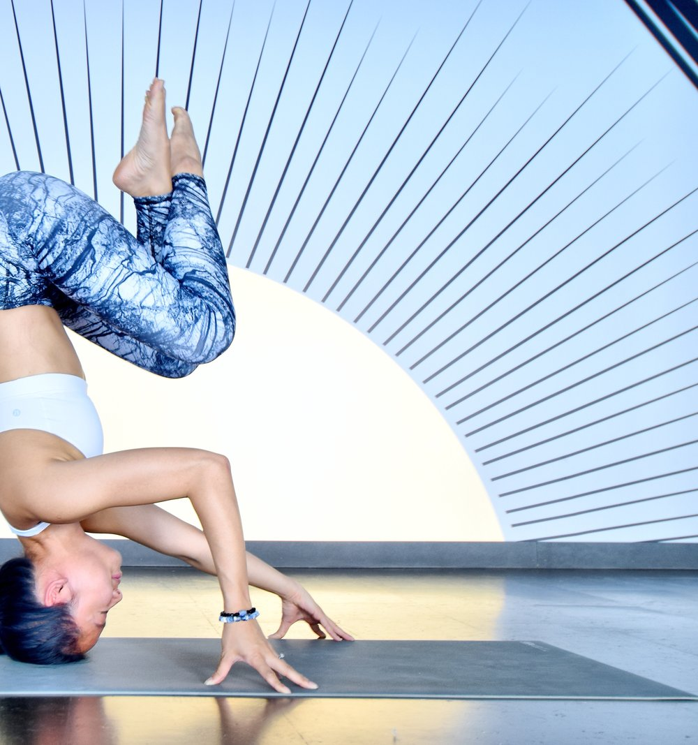 A headstand by Queenie, Toronto yoga teacher, while wearing  Aura sodalite bracelets