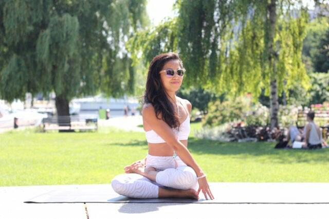 Su Chun  doing a 1/2 lotus with a twist yoga pose, wearing a  white Howlite yoga bracelet by Aura