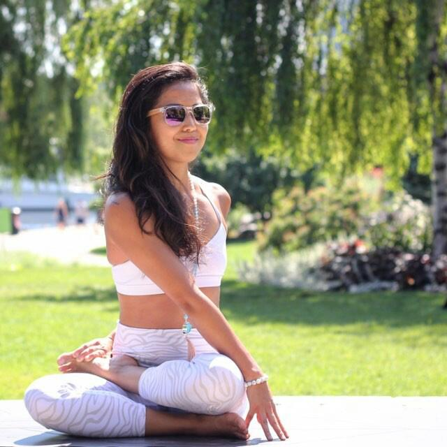 Su doing a half lotus twist with a twist yoga pose in the park - wearing a  white Howlite yoga bracelet by Aura