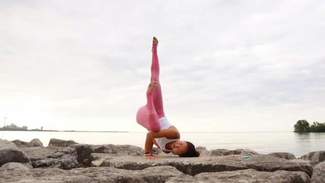 Toronto Yogi, Su, doing a Fallen Angel yoga pose by the water, wearing a white Aura Howlite bracelet
