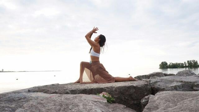 Su from Toronto doing yoga outside by the Lake and wearing a white Howlite yoga bracelet from Aura