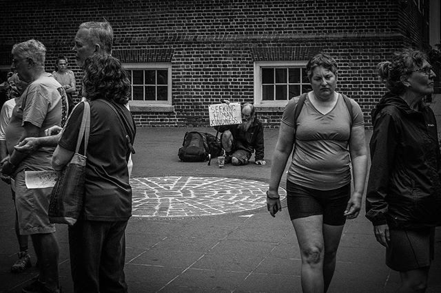 I shot this just a couple weeks ago in Boston. My heart broke before I pressed the shutter. I went and spoke to him, because this scene spoke to me. I wanted to let him know he was noticed, heard and loved. When everyone else has their attention diverted elsewhere, will you see the unnoticed? Hear the unheard? Love the unloved? It's images like this that drove me to launch @throughoureyesproject. Tens of thousands of tourists have passed by this man (apparently he and his signs are pretty iconic) and gone back to their home cities unchanged. There are so many in our towns struggling with homelessness and poverty. It's time to do something more. • • • #worldstreetphotography #thephotosociety #street #photography #streetphotography #street_photography #challengerstreets #world_streets #ig_streetphotography #lensonstreets #capturestreets #everydayeverywhere #street_perfection #photooftheday #streetsinworld #streetart #aspfeatures #bnw #blackandwhite #bwlover #bnw_planet #bnw_captures  #lensculturestreets #everybodystreet #homeless #ThroughOurEyesProject