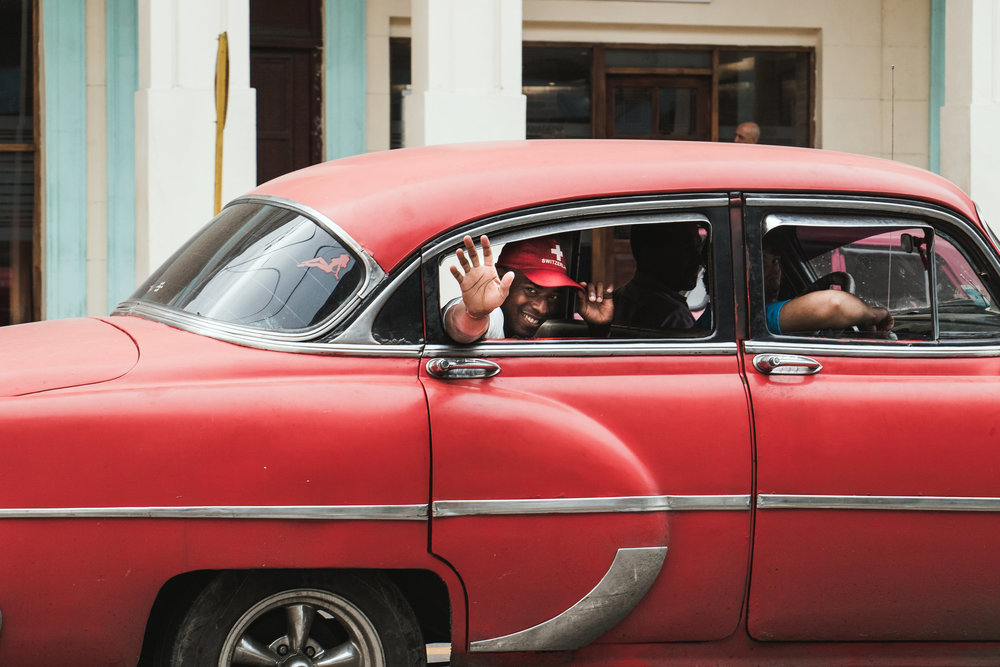 Our salsa instructor, David, drives by in Centro Havana. Photo by Kait Labbate for Comuna Travel.