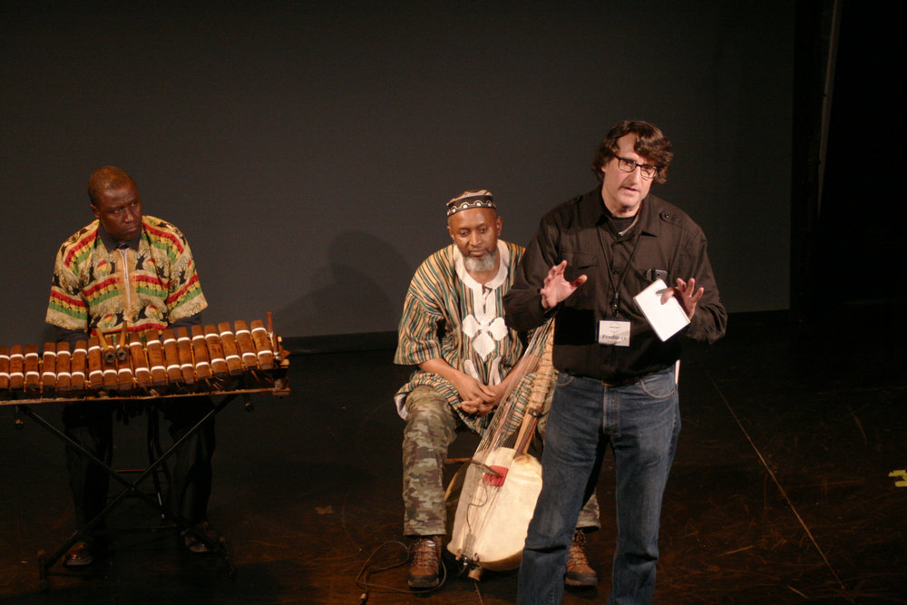 Producer Tom Block introduces the evening, standing in front of the first performers, Ebrima Jassey and Salieu Suso. Photo by Elisa Gutierrez
