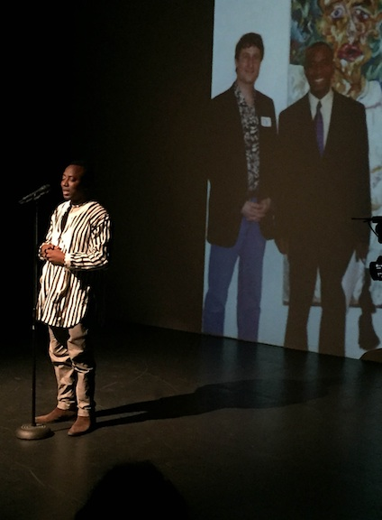 Omoyele Sowore  at the inaugural  International Human Rights Art Festival  at Dixon Place, March 3, 2017. Behind him is a projected image of him and Festival Producer Tom Block, in front of a painting of Mr. Sowore by Mr. Block, in 2002 at the AFL-CIO Headquarters in Washington DC.