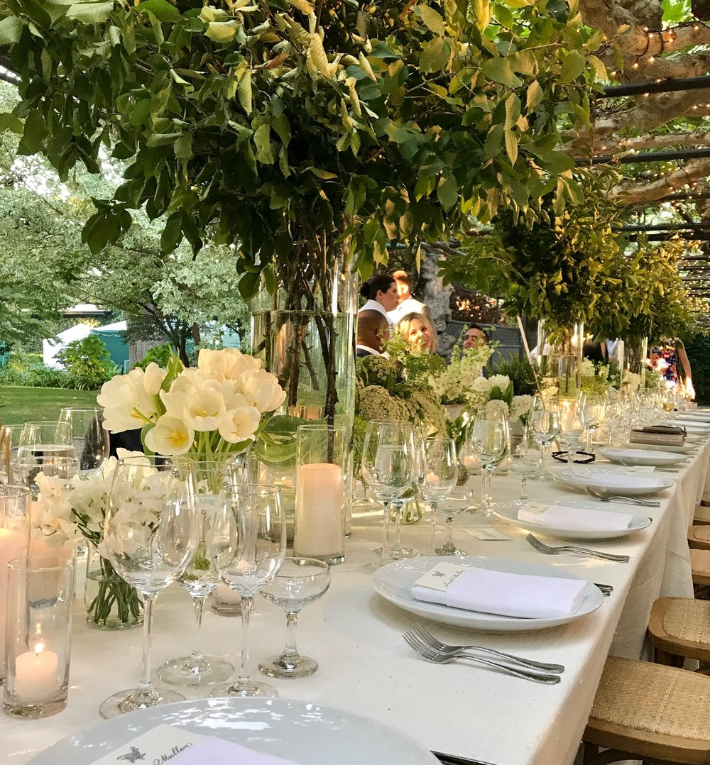 A tablescape to remember. Varying sizes of green and white flowers grace the tables of the bride & groom's friends and families.