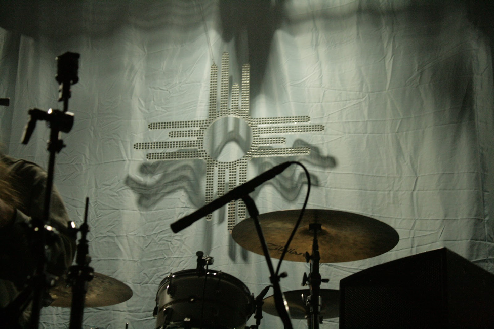 "Photo by Rachel Kupfer. Light reflects off of the mirrors on the Bad Suns logo. The light blue curtain behind it is meant to replicate the blue bed sheets on the cover of the band's album, ""Disappear Here."""