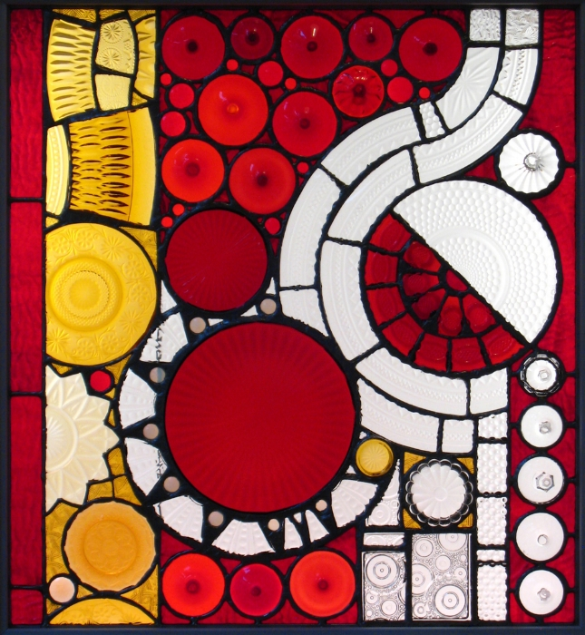 Commission for Margaret Kramer: The centers of old red plates and the bases of red wine glasses were composed alongside pieces of amber and clear glass that were cut from various other glass objects.