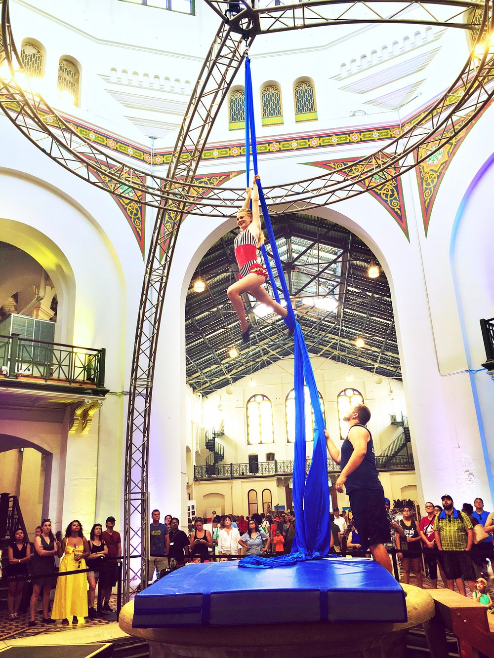 An artist on aerial silks performs at the Circus Arts Smithsonian Folklife Festival while a crowd watches intently.