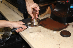 "Coffee grounds are subsequently packed tightly, in a process known as ""tamping,"" into the portafilter to allow water to even distribute throughout the grounds during the brewing process."