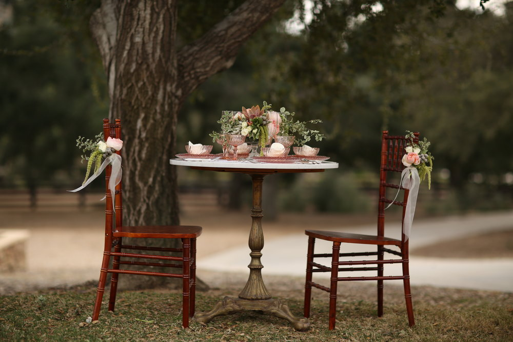 A cozy view of a round marble table with a brass pedestal base and two Chiavari chairs with floral treatments. The perfect sweetheart table for any wedding couple. The table is set with vintage Pink Swirl Depression Glass. All available to rent. Location is at  Chateau Adare  in Murrieta, California.