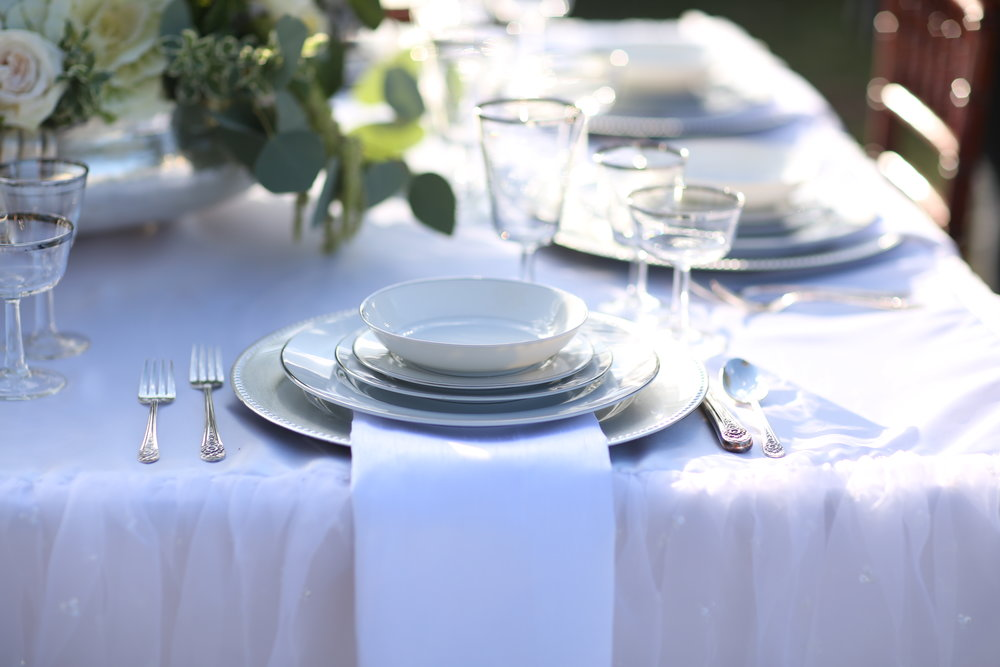 Place setting of silver and white china, complete with silver charge and silver rimmed goblets.