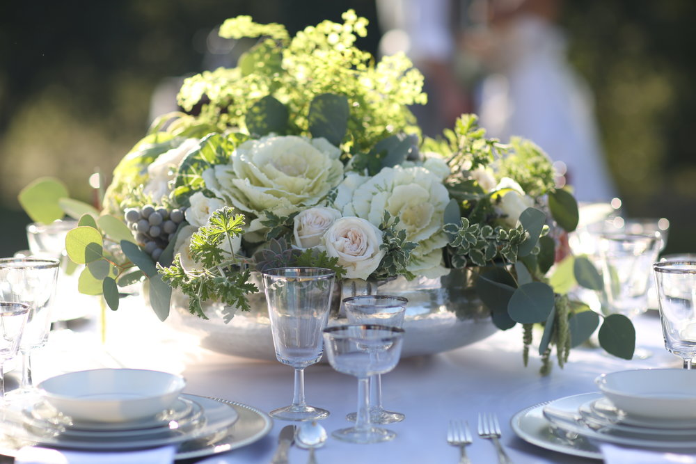 Close up photo of a table set with green and white flowers in a silver urn. Vintage silver and white china with silver rimmed goblets available to rent for wedding and events in the Temecula Valley.