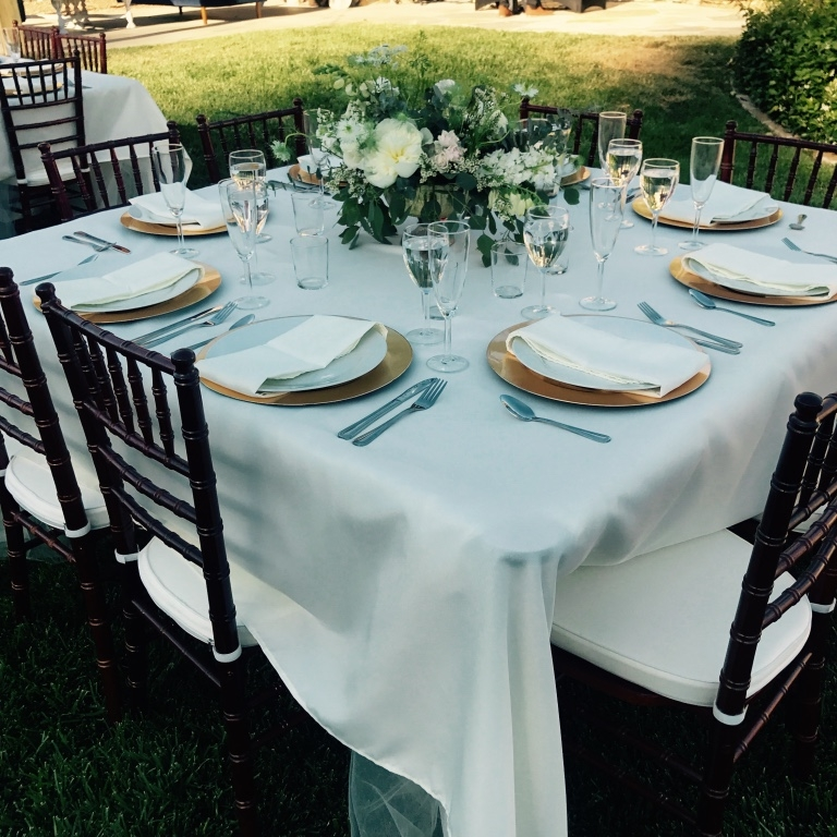 Classic white dinner plates on gold chargers set on a square table with chiavari chairs. Wedding reception in Murrieta part of the Temecula Valley.