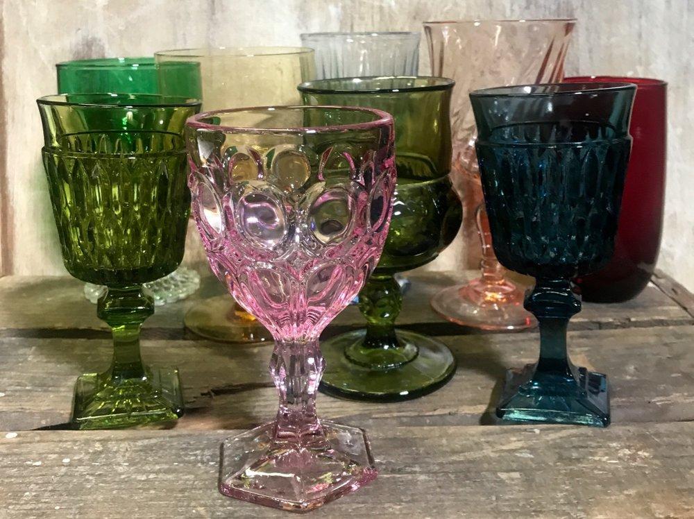 Colorful mismatched vintage glassware goblets. Amber glass, pink glass, blue glass, olive green glass, emerald glass, ruby glass, pink swirl glass. Eclectic