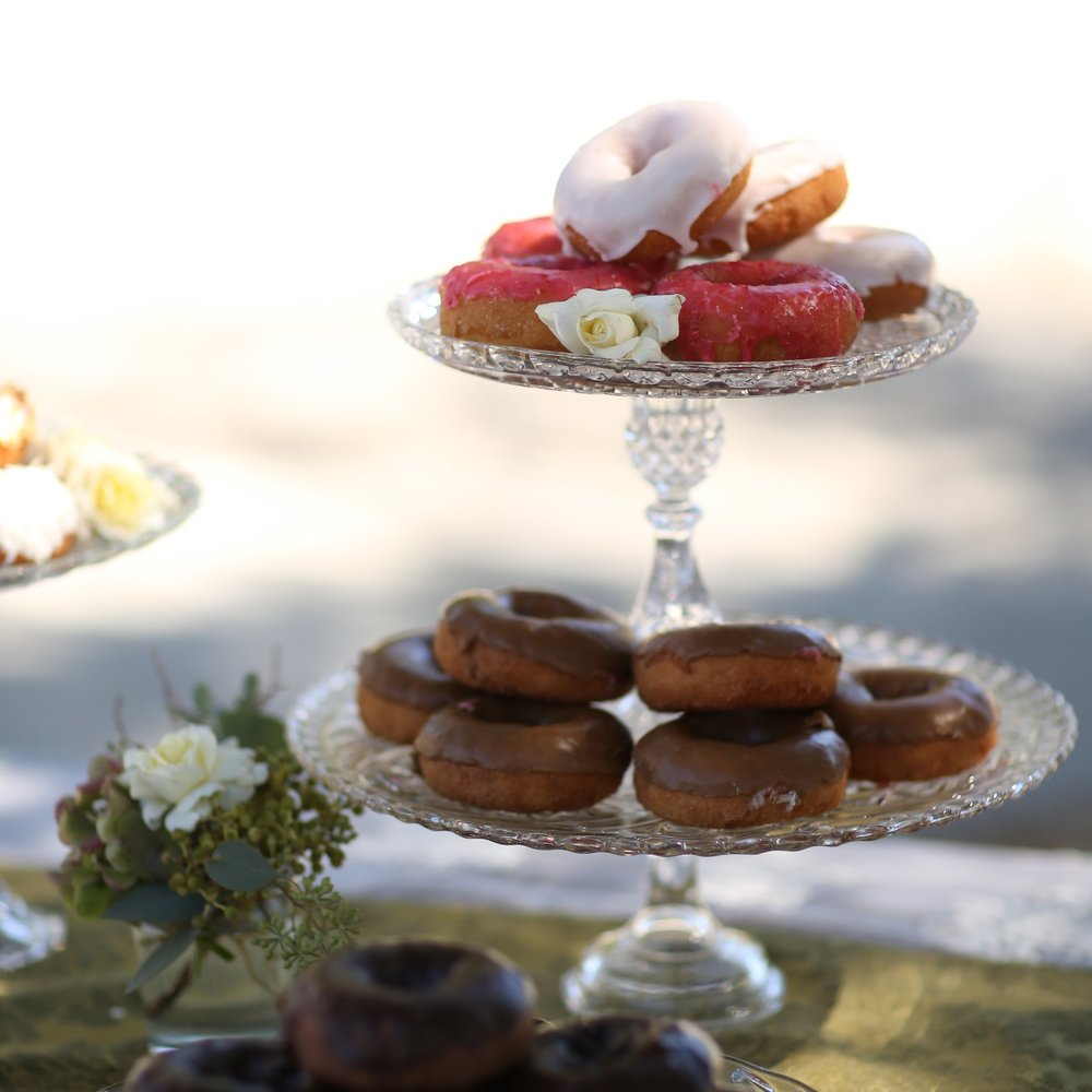Two tiered cut glass pedestal platter with donut desserts.