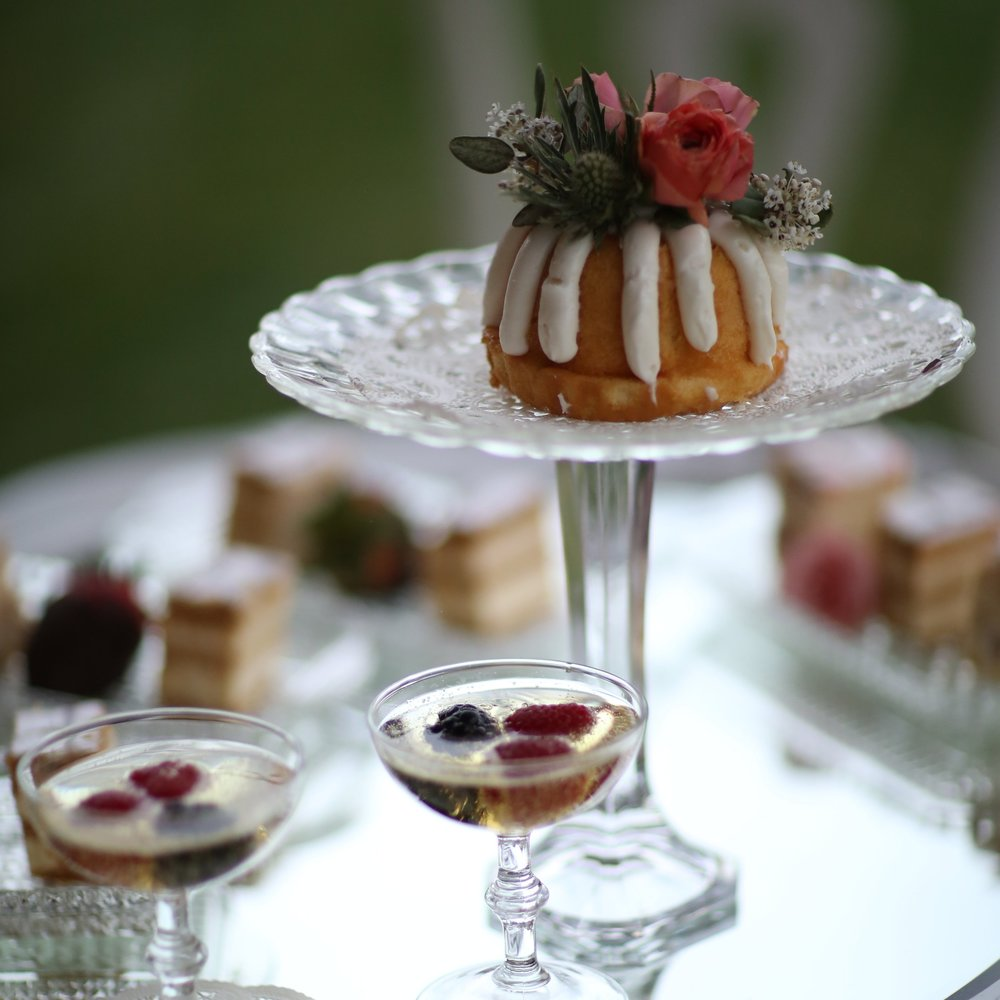 Cut glass pedestal cake plate with small bundt cake. Champaign coupes with floating berries. Assorted desserts on snack sets.