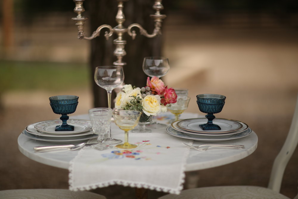 Round marble table with mismatched china and blue and amber goblets. silver candelabra on top of vintage table runner.