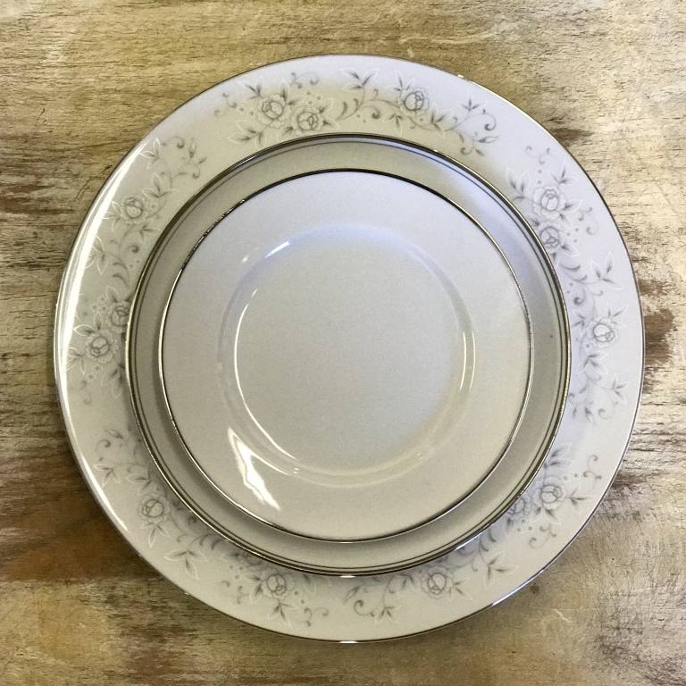 Silver and white mismatched china collection. Dinner plates, salad plates, bread plates, appetizer plates, dessert plates. Vintage Rentals in the Temecula Valley.