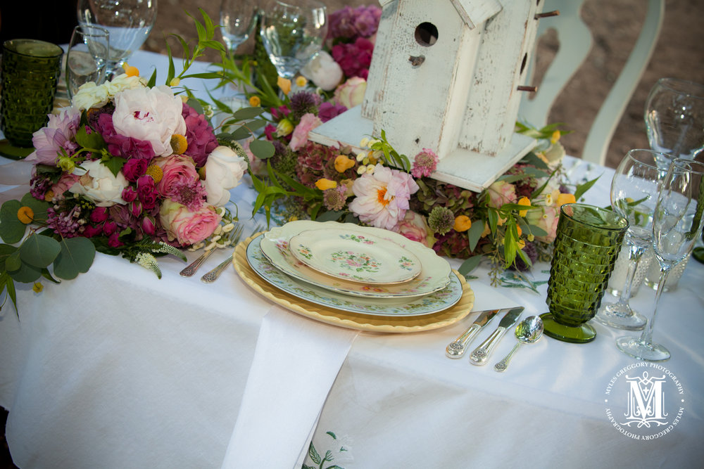 Birdhouse centerpiece with floral treatment.  The table is set with vintage yellow tone china.