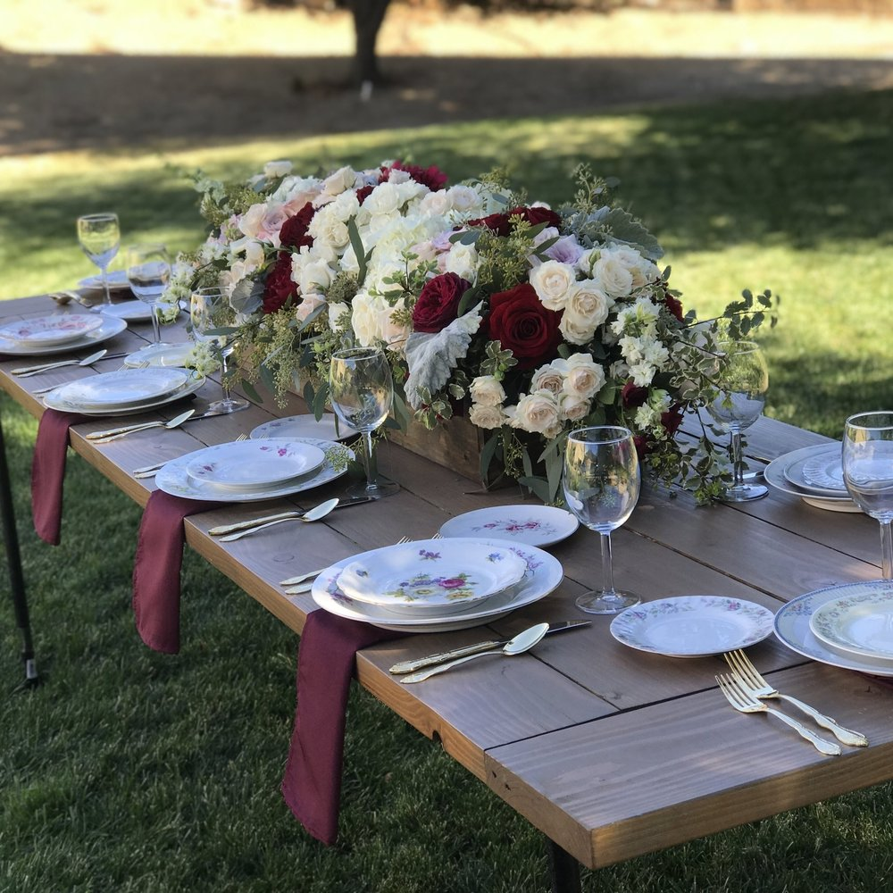 Farm table with floral pink vintage mismatched china. Red wine goblets with gold silverware.  Marsala napkins. Pink roses and marsala peonies in a wooden box planter