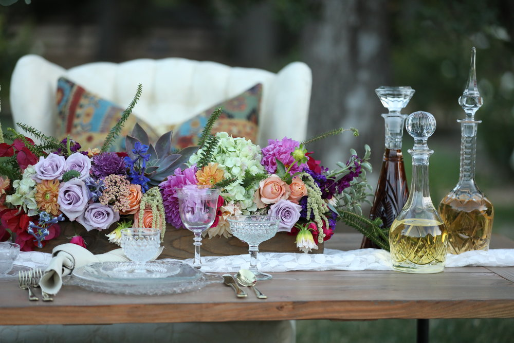 Boho setting with a industrial farm table and cut glass dishes. Vintage decanters and spring floral centerpiece.
