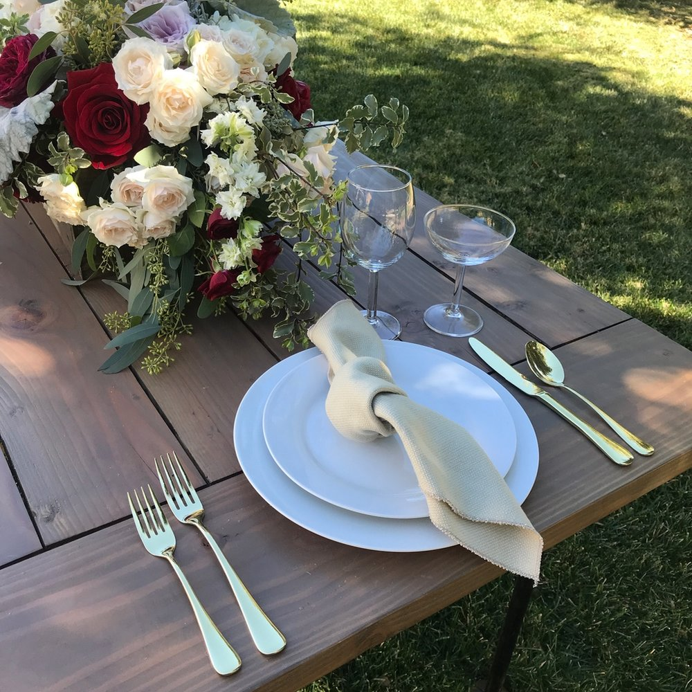 White dinner plates on a large white ceramic charger. Natural linen napkin and gold silverware. Set on an industrial farm table at Chateau Adare in Murrieta.