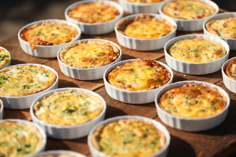 Brunch at a baby shower. A variety of individual quiche in quiche dishes.