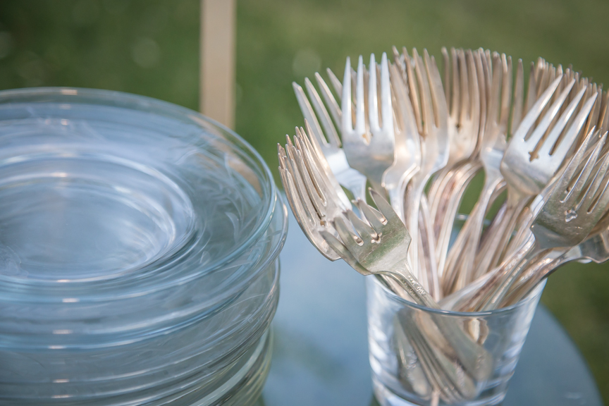 Assorted mismatched silver forks in a glass with vintage glass dessert plates