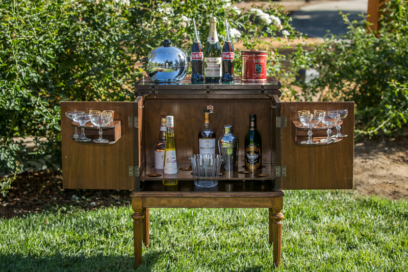 Mid-century modern portable bar filled with libations.  Penguin ice bucket. crystal coupes