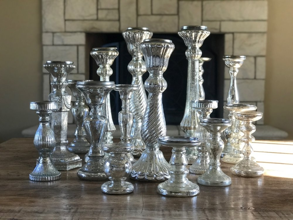 mismatched assorted sizes of mercury glass candlesticks for pillar candles.