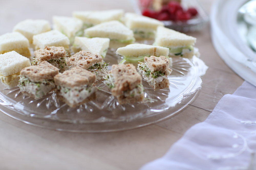 Cut glass platter with small sandwiches on it.
