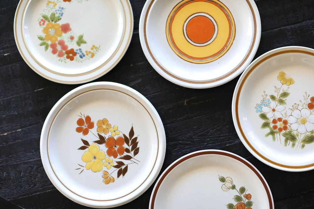Mismatched stoneware dish collection with flowers in orange tones. Vintage 80's dishes for rent.