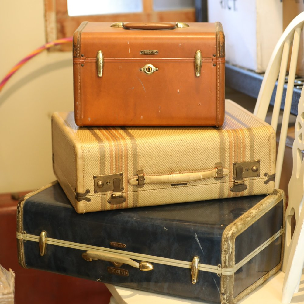 three vintage suitcases on a white wooden dining chair