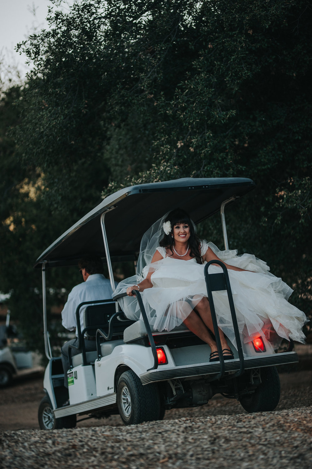 Bride wearing Zac Posen riding in golf cart in the Temecula Valley.