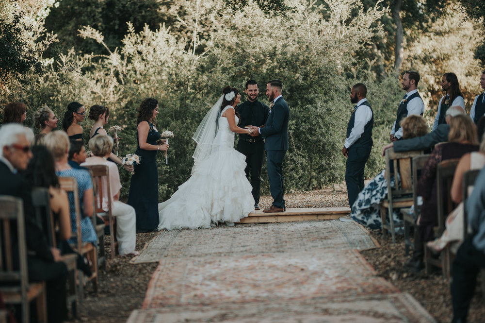 Bride wearing Zac Posen with her groom making her vows in a aisle of vintage rugs in the Temecula Valley.