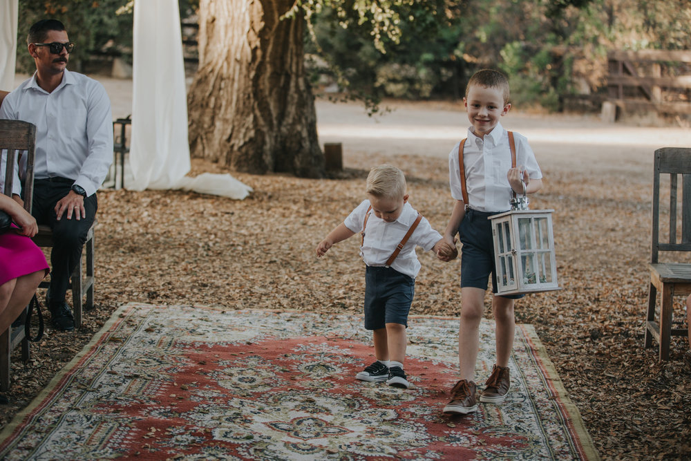 Ring bearers walking down a vintage carpet aisle at a wedding in the Temecula Valley.