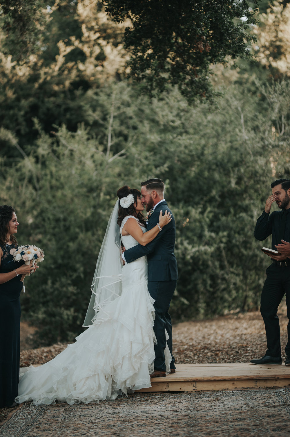 Bride wearing Zac Posen kissing her groom on vintage carpets in the Temecula Valley.