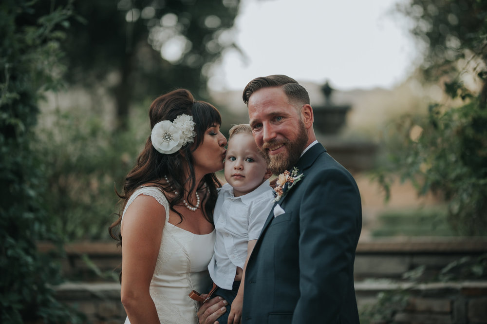 Bride kissing her son with her groom at Chateau Adare in Murrieta.