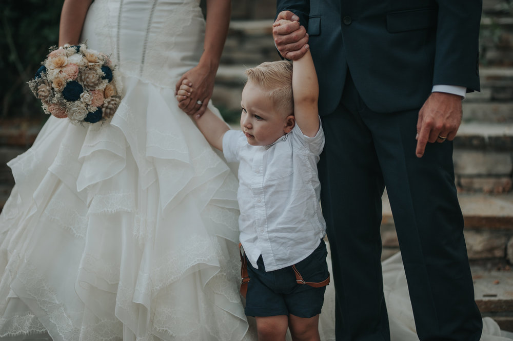 Bride wearing Zac Posen holding wooden flowers with son and groom in the Temecula Valley.