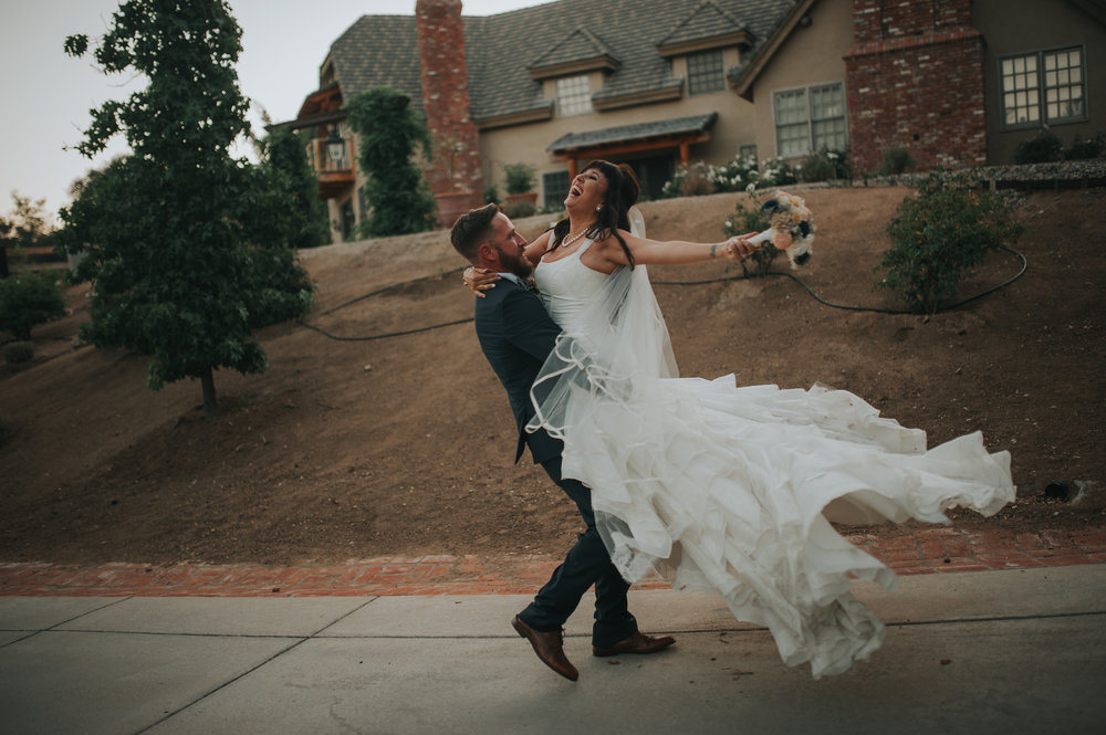 Groom twirling happy bride in front of the Estate Chateau Adare in Murrieta in the Temecula Valley.
