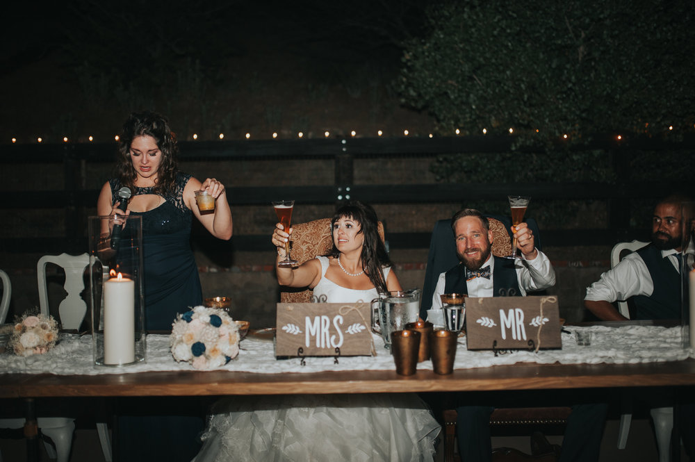 Bride and groom sharing a toast with the maid of honor at a wedding reception in the Temecula Valley.