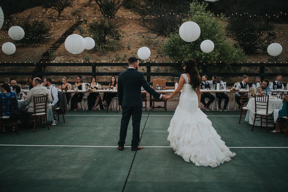 Zac Posen dress train on bride at Murrieta wedding reception. Groom holding her hand.