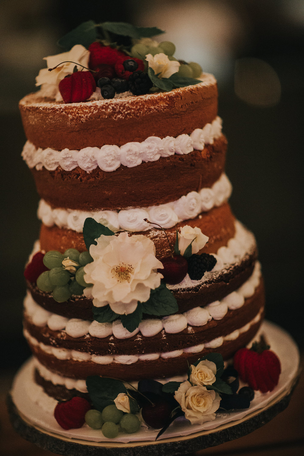 Naked wedding cake topped with fresh fruit and flowers made by a local vendor in the Temecula valley.