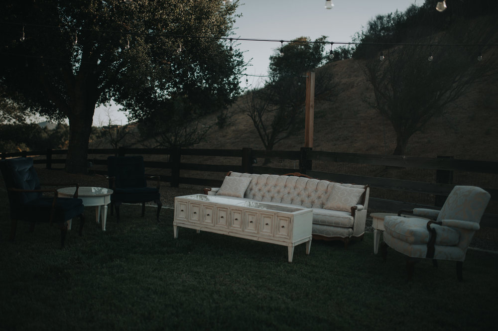 Lounge area at a wedding reception in the Temecula Valley. Cream colored tufted couch with a mid century modern coffee table.