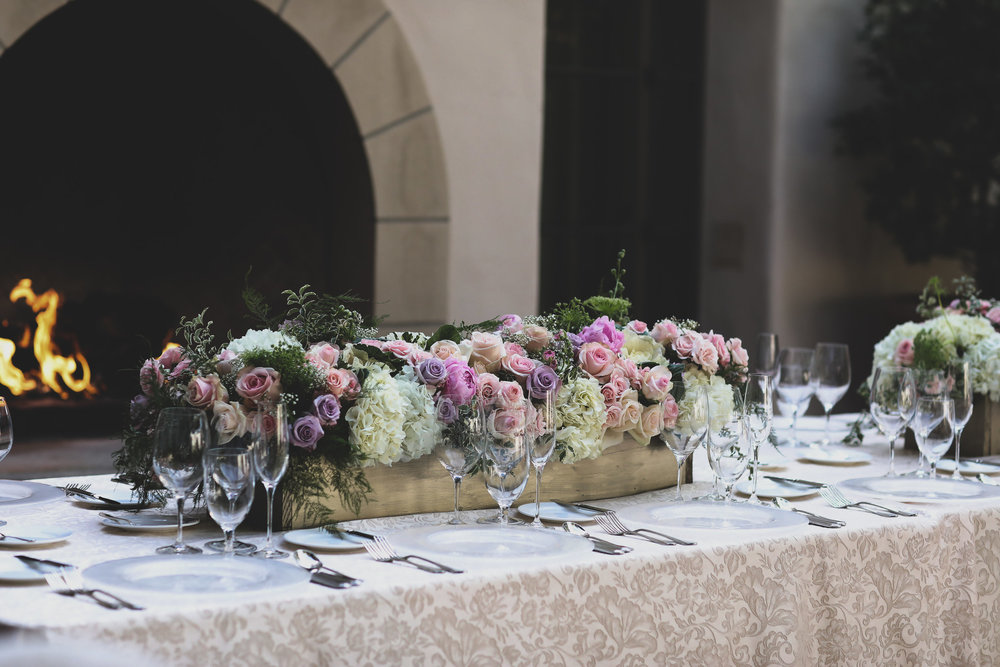 Intimate wedding table centerpiece on a brides table at the Resort at Pelican Hill. The floral arrangement consists of pink and lavender roses and white hydrangeas.